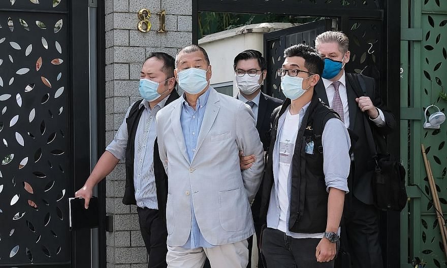 Hong Kong media tycoon Jimmy Lai being led away from his residence by law enforcement officials in Hong Kong yesterday. One of the city's most prominent democracy activists and an ardent critic of Beijing, Lai was taken to his office later in handcuf