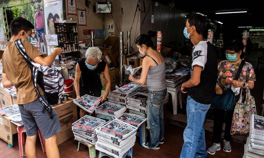 A vendor (second from left) selling copies of the Apple Daily at a newsstand in Hong Kong yesterday, a day after the city's authorities arrested the tabloid's owner. PHOTO: AGENCE FRANCE-PRESSE
