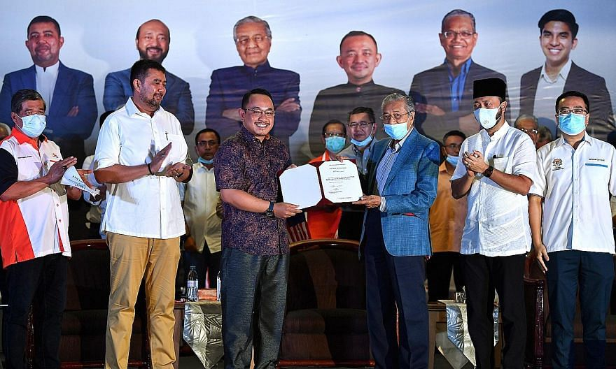 Tun Dr Mahathir Mohamad (in blue jacket) giving a letter of appointment on Wednesday to Mr Amir Khusyairi Mohamad Tanusi, who will be contesting the Aug 29 by-election in Perak. PHOTO: BERNAMA