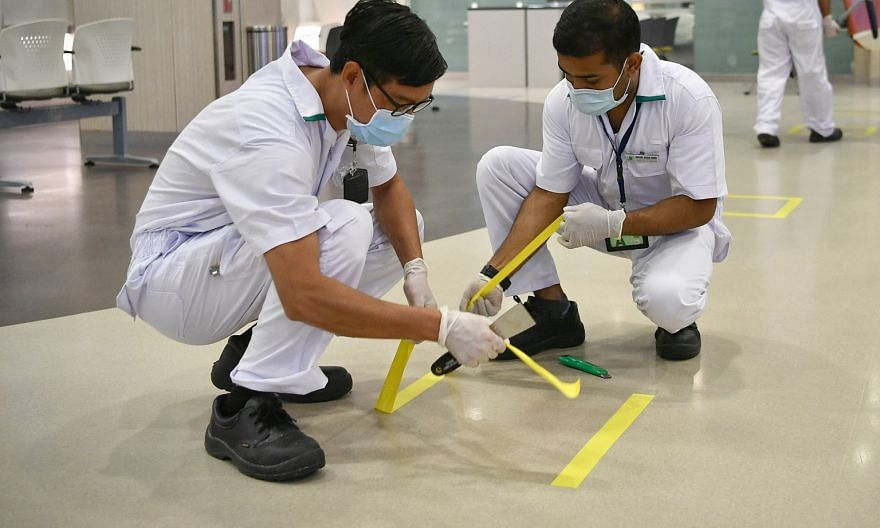 Technicians using tape as safe distancing markers in the pharmacy at Singapore General Hospital last Tuesday.