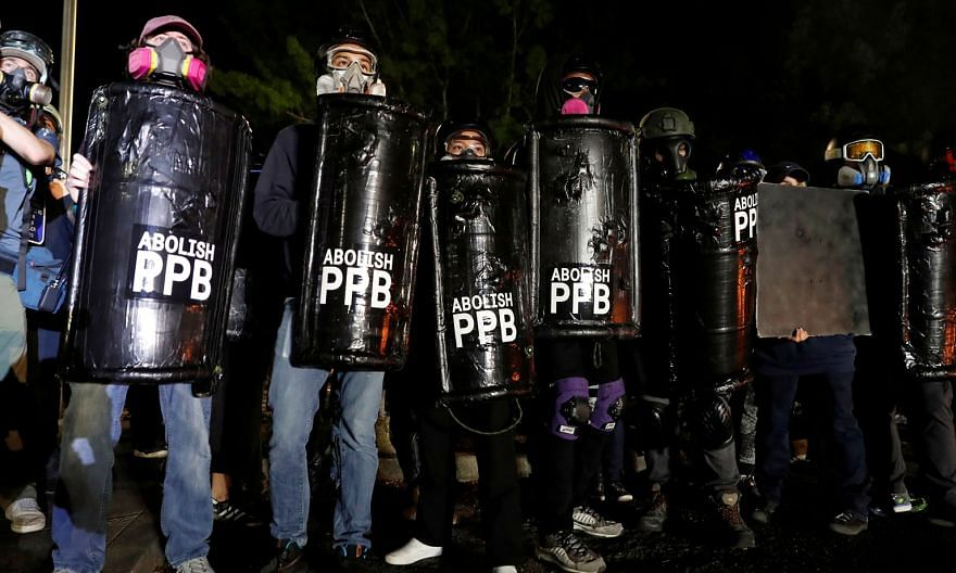 Protesters carrying shields calling for the abolition of the Portland Police Bureau (PPB) during a rally in Portland on Sunday. The police said demonstrators lit fires and attacked officers with lasers, rocks and bottles. PHOTO: REUTERS