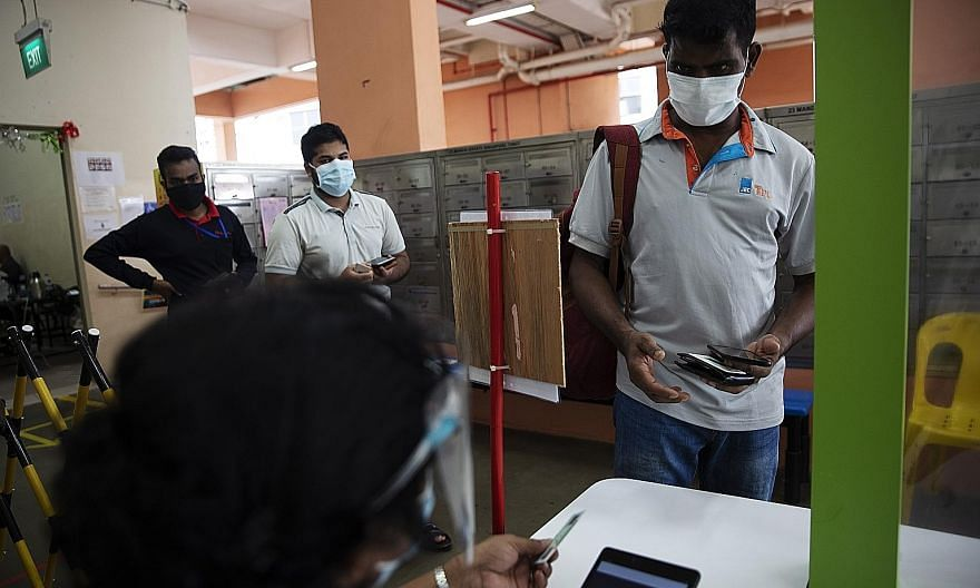 Migrant workers showing their ID cards and green AccessCode as they leave for work at Westlite Juniper dormitory. The green AccessCode indicates that the workers have fulfilled several requirements, including that they have tested negative for Covid-