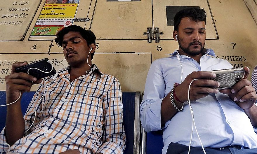 Commuters on a Mumbai suburban train. India's telecom industry has over the past two decades transformed the lives of millions of Indians to the point where even the poor can afford a phone and a connection. But many companies, ridden by debt and tou