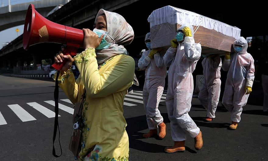 Government workers in protective gear carrying a mock-up of a coffin of a Covid-19 victim on a main road in Jakarta to warn people about the dangers of the virus in the midst of the pandemic. A resurgence of cases will soon put doctors in the positio