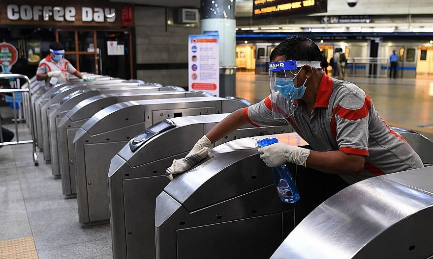 An employee sanitising entrance gates at Rajeev Chowk metro station in New Delhi yesterday, as metro services prepare to resume on Monday after a five-month hiatus. PHOTO: AGENCE FRANCE-PRESSE