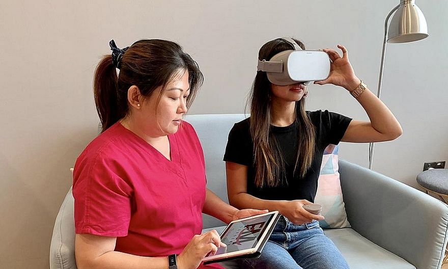 Nurse Chong Pei San with a patient who is watching a virtual-reality video on breast wide excision and sentinel lymph node biopsy through a headset.