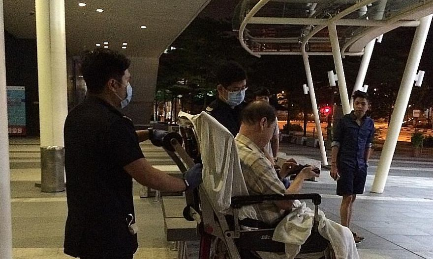 Mr Ng Tee Kian being taken for treatment after he slipped and fell outside a retail unit at Fusionopolis One in 2016. He sued the facilities manager for the building for negligence, but the court stand-off was averted when the defendant accepted 60 p