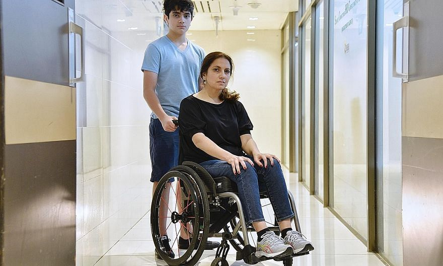 Ms Valencia Zuniga, seen here with her youngest child Emilio Klenner, 14, uses a wheelchair as a result of an alleged botched operation.