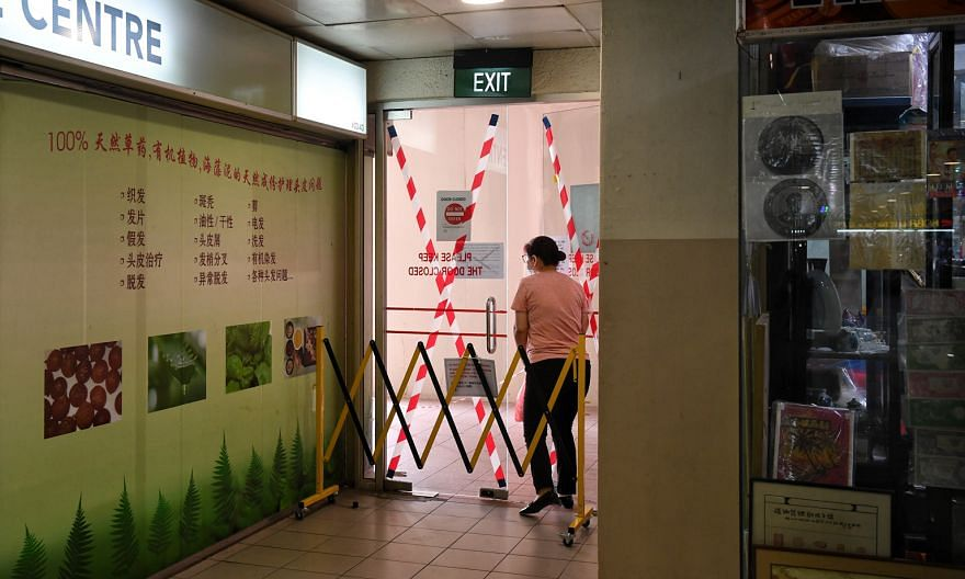 A woman skirting a movable barricade to access the doors for entry to and exit from the third floor of People's Park Centre last week. The mall was one of 16 found by the Singapore Civil Defence Force to have breached fire safety requirements by padl