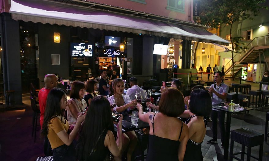 Patrons at Le Noir in Clarke Quay on March 25, before the circuit breaker. The bar is among seven F&B outlets in popular nightspots that were fined $1,000 each for failing to comply with safe distancing rules over the weekend. It will also be suspend