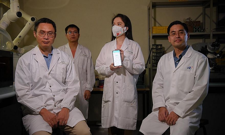 The team behind the smart mask system - (from far left) Professor Chen Xiaodong, research fellows Liang Pan and Wang Cong, and Professor Loh Xian Jun. Ms Wang is wearing the smart mask, which allows the wearer's real-time health data to be transmitte