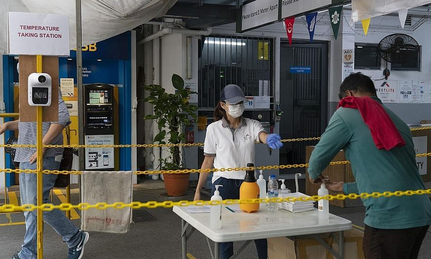 Measures at the Westlite Mandai dormitory include hand sanitiser and temperature checks at the entrance, and safe distancing markers placed on the floor (below) at the grocery store in the dormitory. One operator called for a coordinated effort with