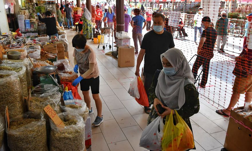 People shopping inside Geylang Serai Market yesterday while snaking queues formed outside to enter. It is one of four wet markets that had imposed entry curbs allowing people to visit only on odd or even dates. Starting yesterday, weekend curbs were