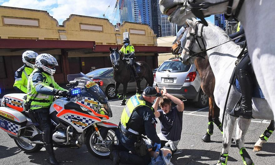 The police detaining an anti-lockdown protester at a rally in Melbourne's Queen Victoria Market yesterday.