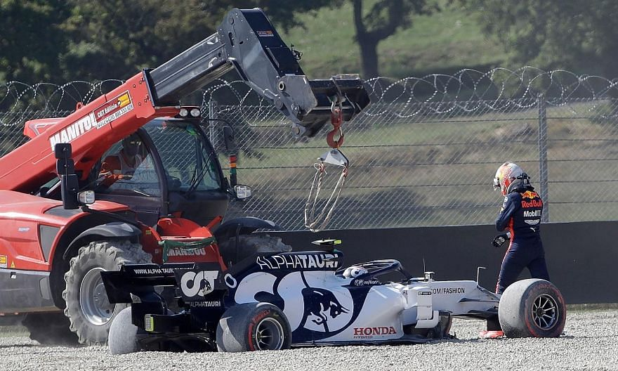 Red Bull's Max Verstappen walking past the car of AlphaTauri's Pierre Gasly after crashing out of the race. PHOTO: REUTERS