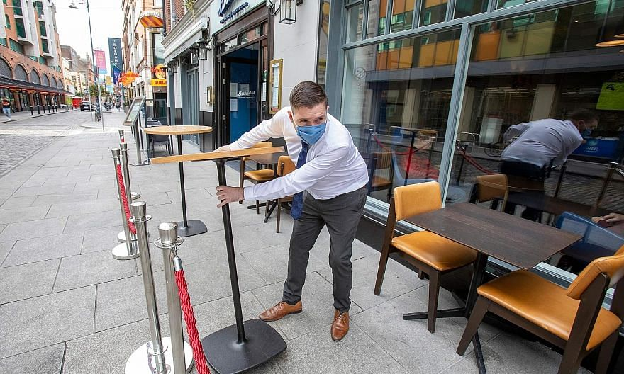 An employee setting out tables outside a pub as restrictions were tightened in Dublin for the second time in a week on Friday.