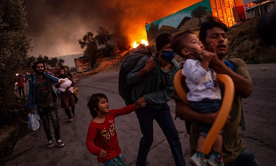 A family of migrants fleeing the Moria camp on the Greek island of Lesbos on Sept 9 after a fire broke out. European Union countries have long been at loggerheads over how to handle the influx of migrants.