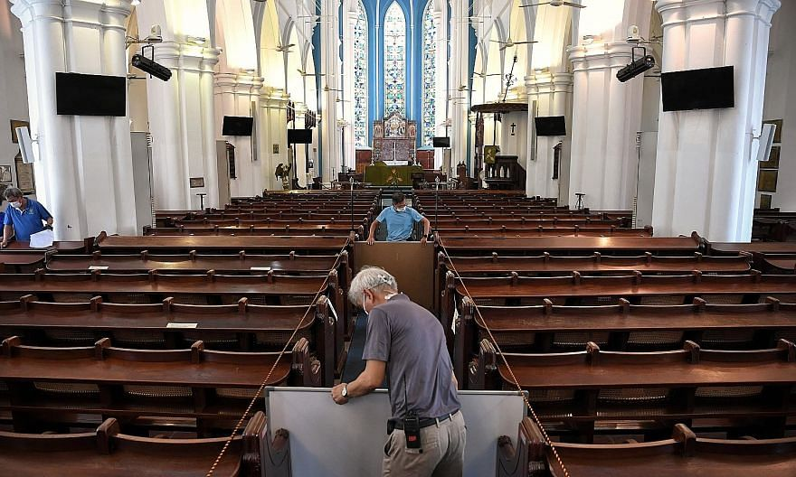 Church staff putting up temporary boards at St Andrew's Cathedral last month to prepare for reopening for a weekend service. The church was among some religious organisations which were allowed to hold gatherings of up to 100 people under a pilot sch