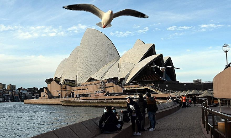 Visitors near Sydney Opera House in Australia. The government's Covid-19 curbs have taken a steep toll on the economy, with tough restrictions forcing many small businesses to shut.