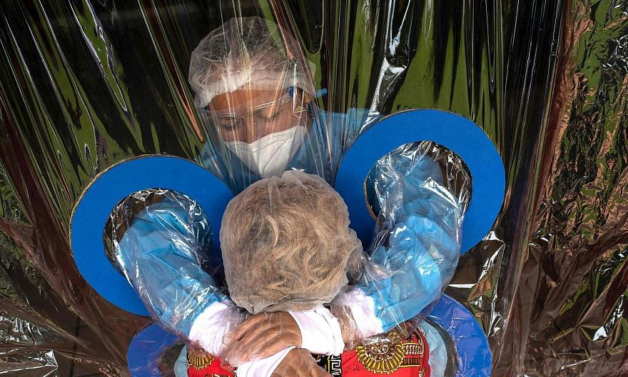 Ms Maria Hernandez, 38, embracing her aunt through a plastic curtain at a nursing home in San Salvador, El Salvador, earlier this month. Dr Michael Ryan from the WHO has suggested the disparate performances of different countries in handling the pand