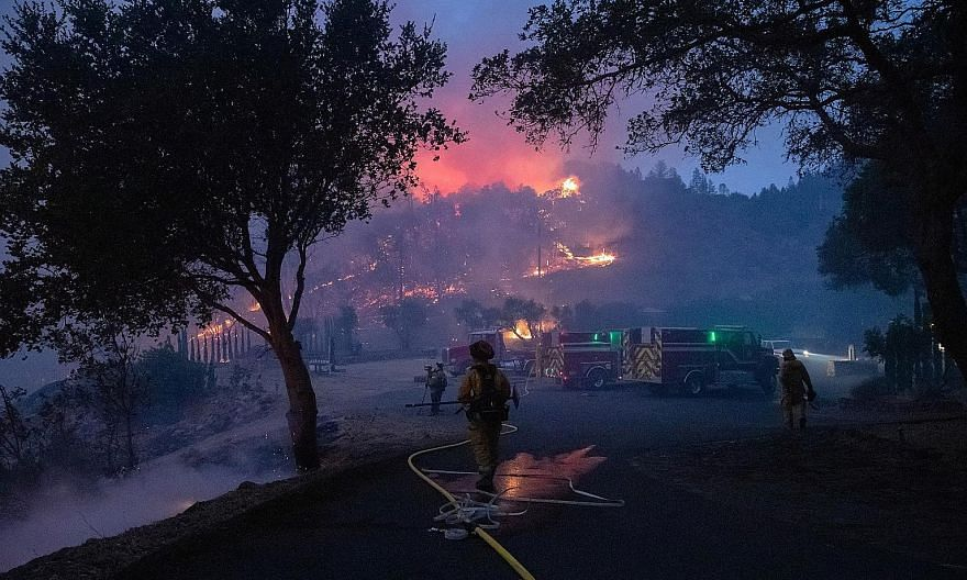 Firefighters battling the Glass Fire as it encroached upon a vineyard in Deer Park, California, on Sunday. The blaze erupted midway through the traditional grape-harvesting period in the Napa Valley, world renowned as one of California's premier wine