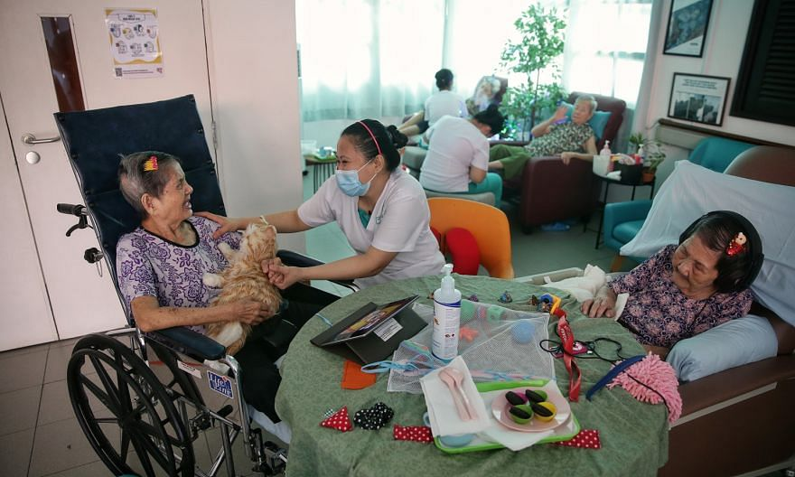 Madam Tang Nyuk Lin (left, with an interactive toy cat) and Madam Khoo Chui York (right, wearing headphones) at Apex Harmony Lodge. The home, which cares for dementia patients, is rolling out a project called Namaste Care, which among other things gi