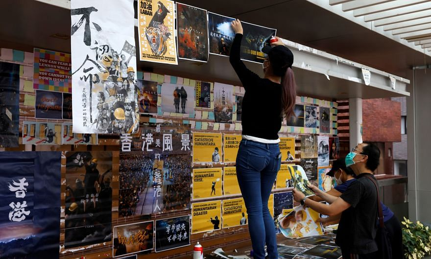 University of Hong Kong students putting up posters on campus yesterday to promote the upcoming pro-democracy protest and demand the release of 12 Hong Kongers under detention in Shenzhen. PHOTO: REUTERS