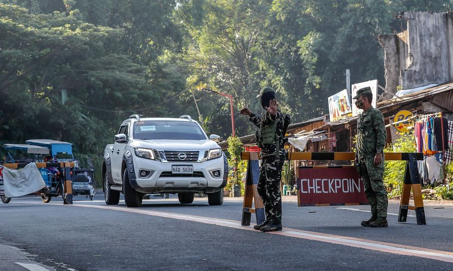 Soldiers directing traffic in Tanay, east of Manila, yesterday. More trains, buses and jeepneys have been allowed to ply their routes in the Philippines.