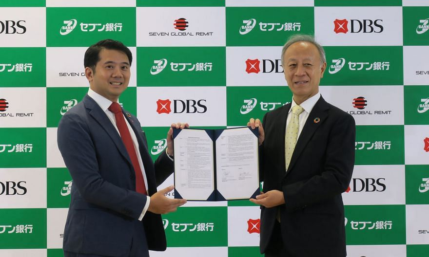 Seven Bank president Yasuaki Funatake (right) and DBS Japan country head Ken Foo with the memorandum of understanding on the deal. ST PHOTO: WALTER SIM