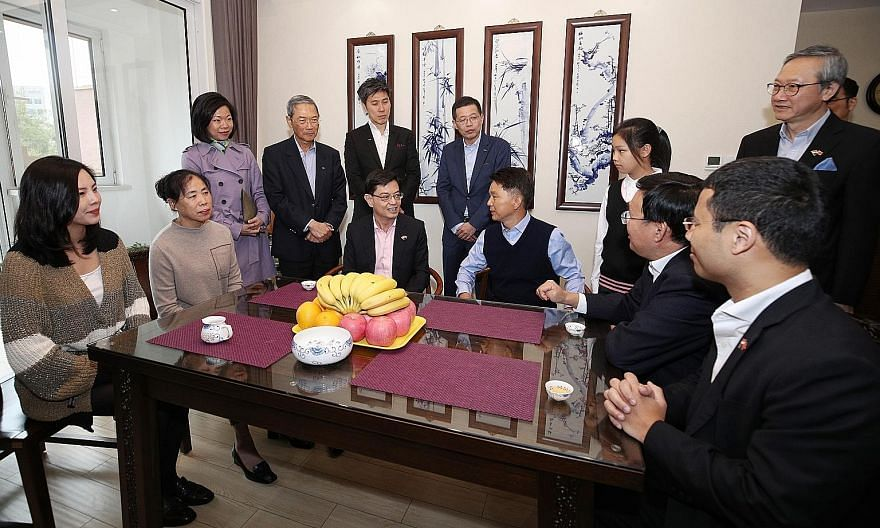 Deputy Prime Minister Heng Swee Keat with Mr Zhang Yuzhuo (seated, second from right), Party Secretary of the Tianjin Binhai New Area District Committee, as they visited a family living in Seasons Garden, a residential project developed by Keppel Lan