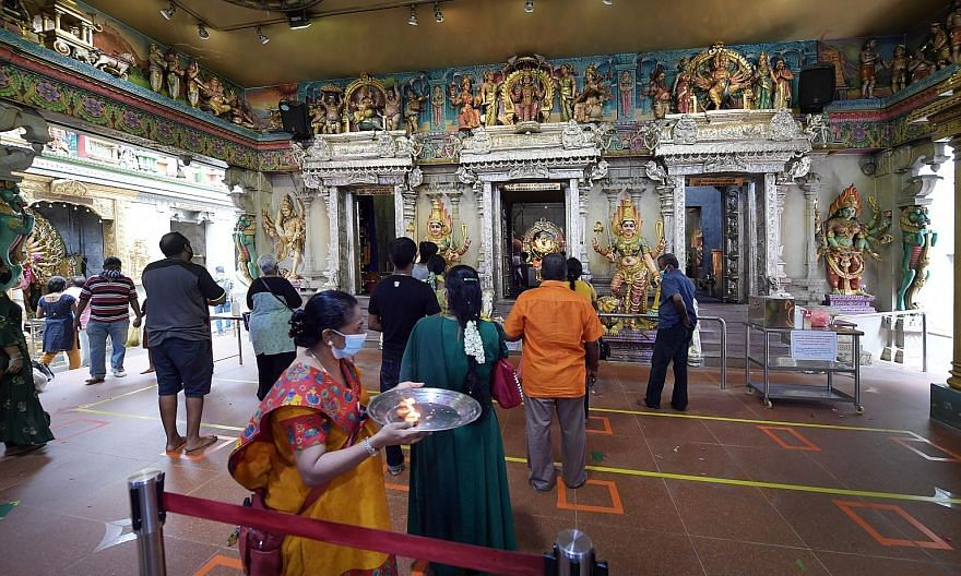 Left: Devotees praying outside Kwan Im Thong Hood Cho Temple, which remained closed yesterday. Far left: Worshippers at Sri Vee-ramakaliamman Temple in Little India yesterday finally got to attend prayers where live music was played.