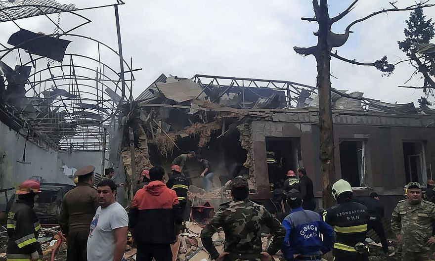 Emergency personnel working in a damaged area of Ganja. Armenia yesterday said it struck a military airport in Azerbaijan's second largest city during the ongoing fighting between the two former Soviet republics over the breakaway Nagorno-Karabakh re