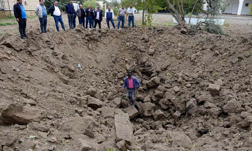 People inspecting a crater yesterday in the town of Beylagan, Azerbaijan. Locals said it was caused by an Armenian rocket strike.