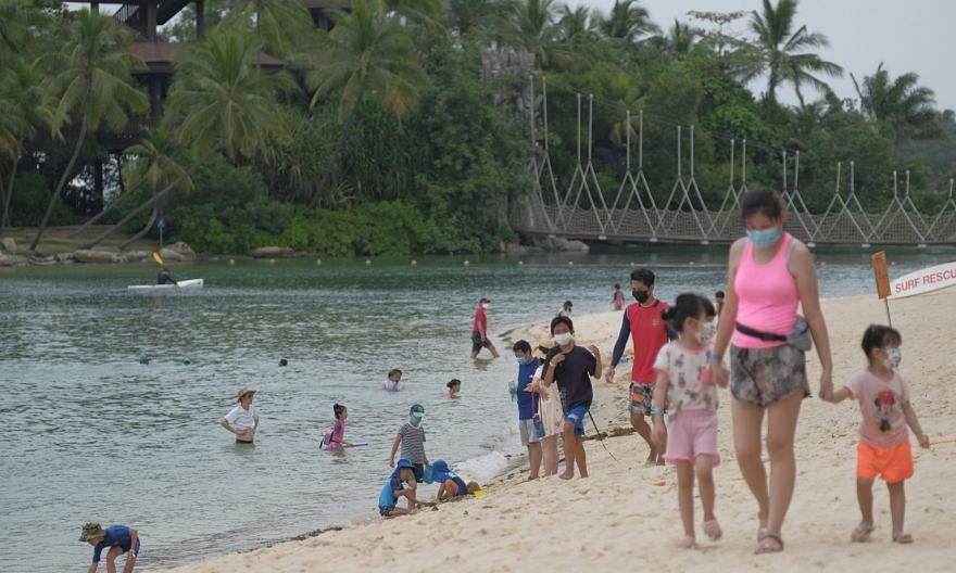 People yesterday at Palawan Beach, where visitors were issued with wristbands upon admission. A Sentosa Development Corporation spokesman said wristbands have been progressively introduced to familiarise Sentosa's beachgoers with the upcoming booking