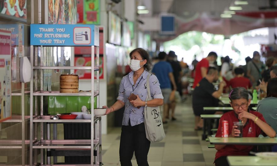 A woman taking a used bowl to the return station at a hawker centre. New mandatory sanitation standards in the Environmental Public Health (Amendment) Bill, which was passed in Parliament yesterday, include cleaning of high-touch surfaces at least on