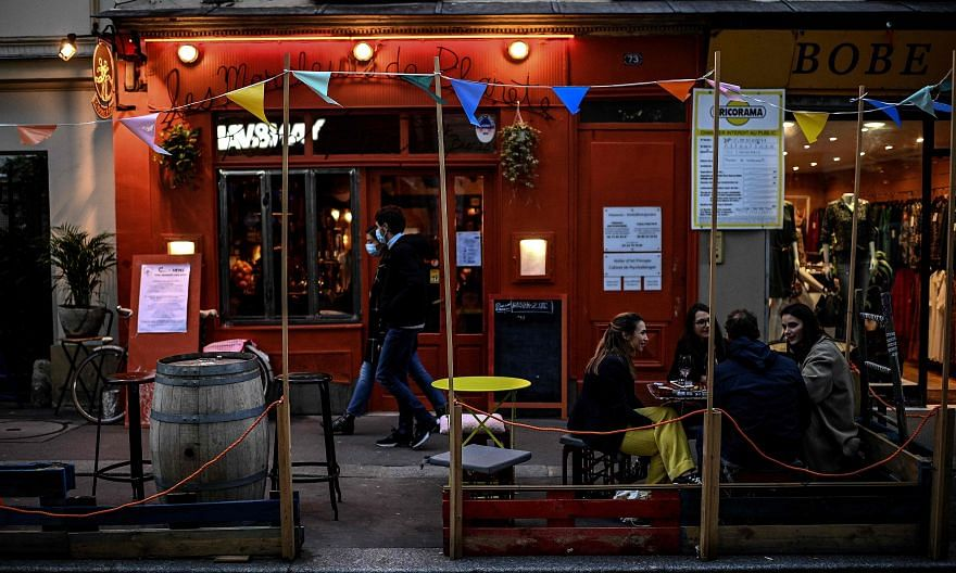 People at a bar in Paris last Saturday. Bars in the French capital have to close for two weeks from today and restaurants must put in place new sanitary protocols to stay open, under the reinforced curbs.
