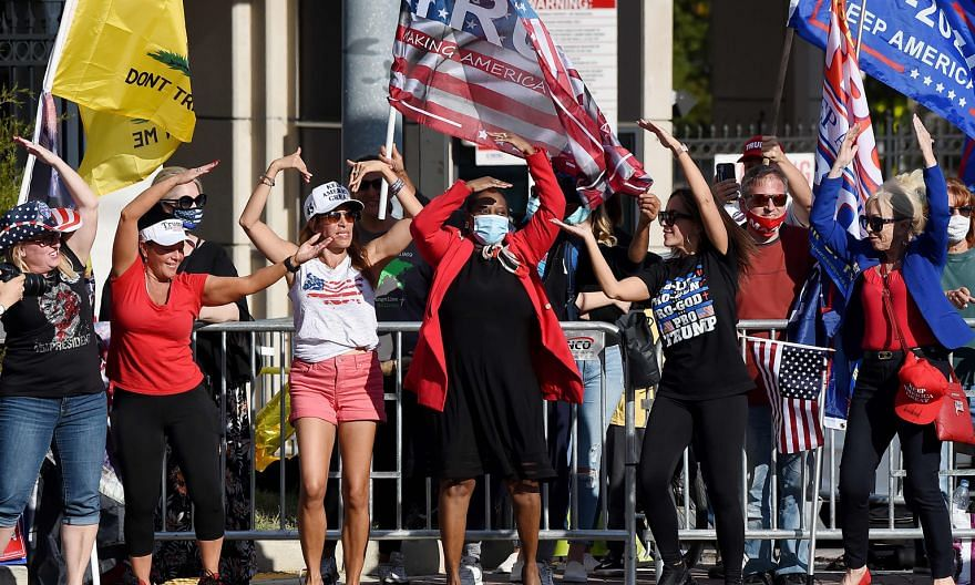 Above: Supporters of Mr Trump outside the Walter Reed National Military Medical Centre in Washington on Monday. As he left the hospital, the President declined to answer questions shouted out by the media.