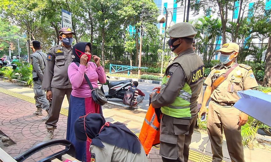Public order officer Lana Hardinata (holding orange vest) advising a street vendor in Jakarta to put on her mask properly and keep a safe distance from her customers.