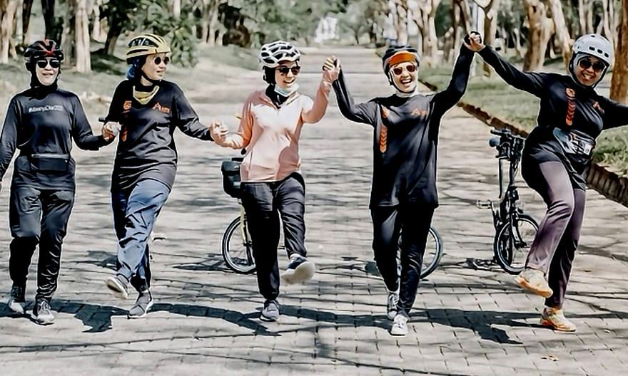 """A group of Indonesian housewives posted a photo of them on a cycling trip. Only one had a mask but it was lowered. One of them told The Straits Times: """"We have known each other for very long and we have been staying in touch constantly... We are all"""