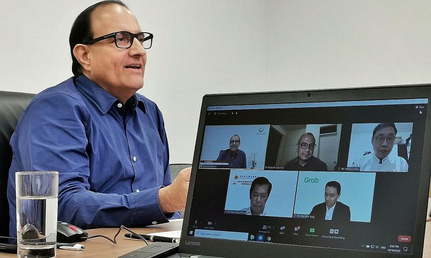 Communications and Information Minister S. Iswaran yesterday interacting with the other panellists at the virtual dialogue (on monitor screen, clockwise after Mr Iswaran): Associate Professor Kenneth Paul Tan of NUS' Lee Kuan Yew School of Public Pol