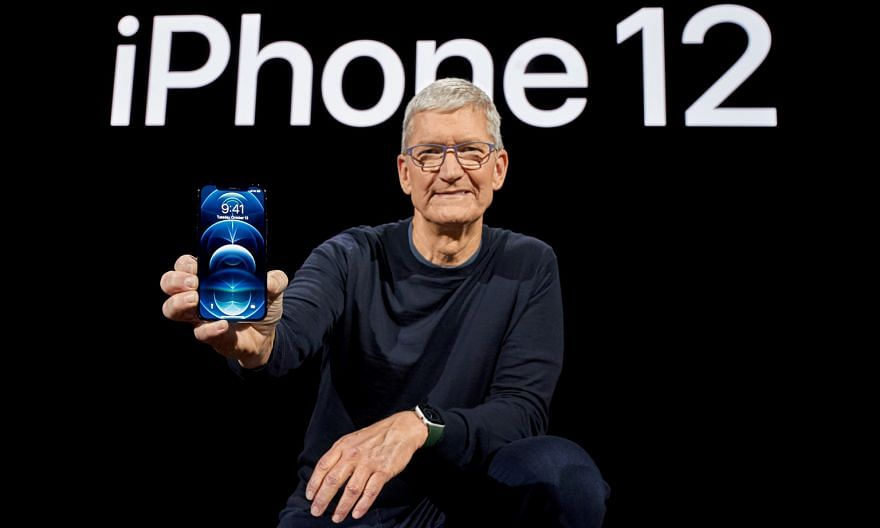 Apple chief executive Tim Cook with one of the brand's new 5G smartphones, the iPhone 12 Pro.