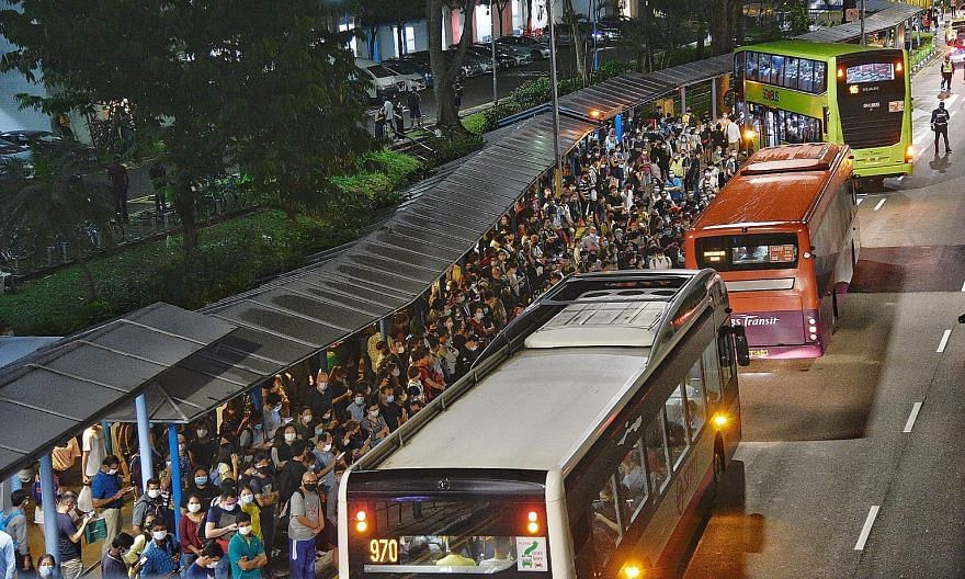 "Crowds gathered at the bus stop outside Queenstown MRT station on Wednesday night after a disruption that affected three lines. SMRT said it is working with the Land Transport Authority to conduct a full investigation into the ""premature failure"" of"