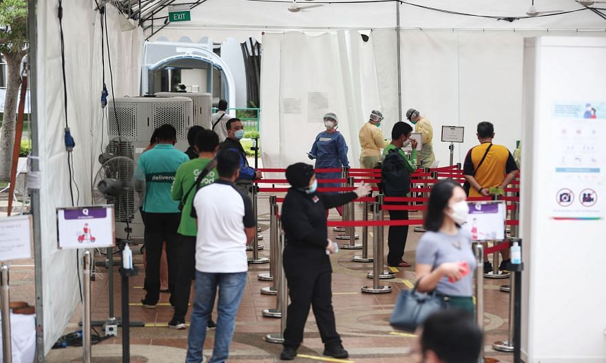 Employees and stallholders at hawker centres and coffee shops, as well as food delivery riders, queueing to be tested for Covid-19 in Marine Parade last month in a pilot swab-testing initiative.