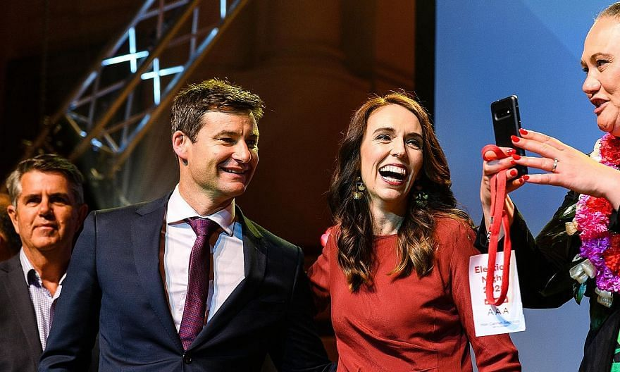 "Above: New Zealand opposition leader Judith Collins congratulated Prime Minister Jacinda Ardern (right, in red) on an ""outstanding"" result yesterday. Right: Ms Ardern with her partner Clarke Gayford at Auckland Town Hall last night. She said Labour's"