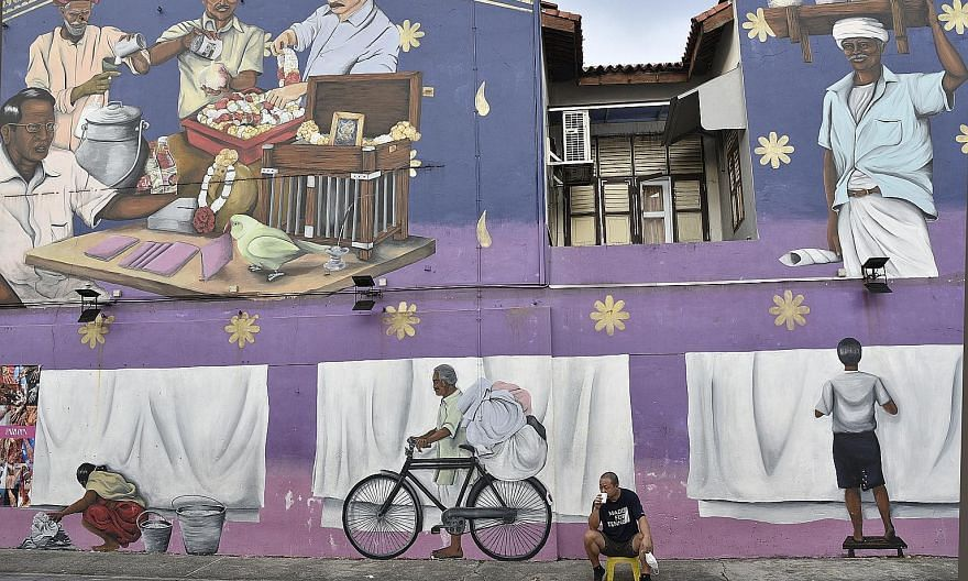 """Migrant workers walking past a mural titled Layers by Shah Rizzal in Serangoon Road. The piece, which depicts traditional shophouses, was created for the 2018 edition of Artwalk Little India, an annual public arts project. There is plenty of """"camera"""