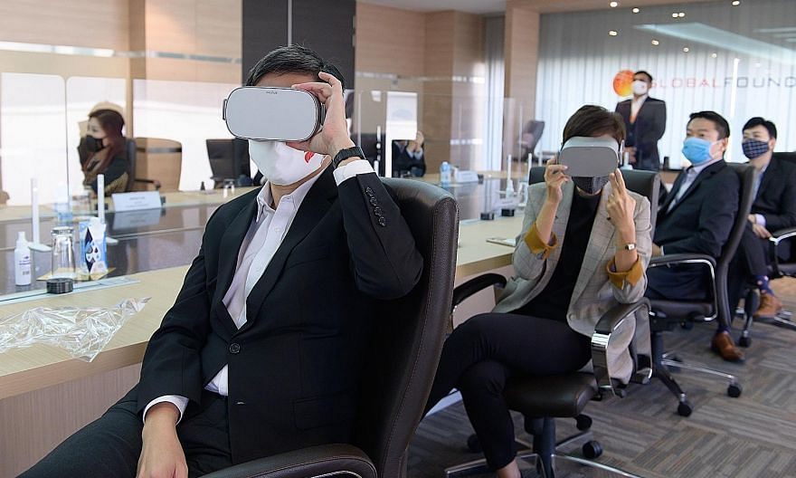 Minister for Trade and Industry Chan Chun Sing and Minister for Manpower Josephine Teo donning headsets to experience a virtual reality tour of the GlobalFoundries Singapore facility during their visit to the semiconductor firm yesterday. PHOTO: MINI