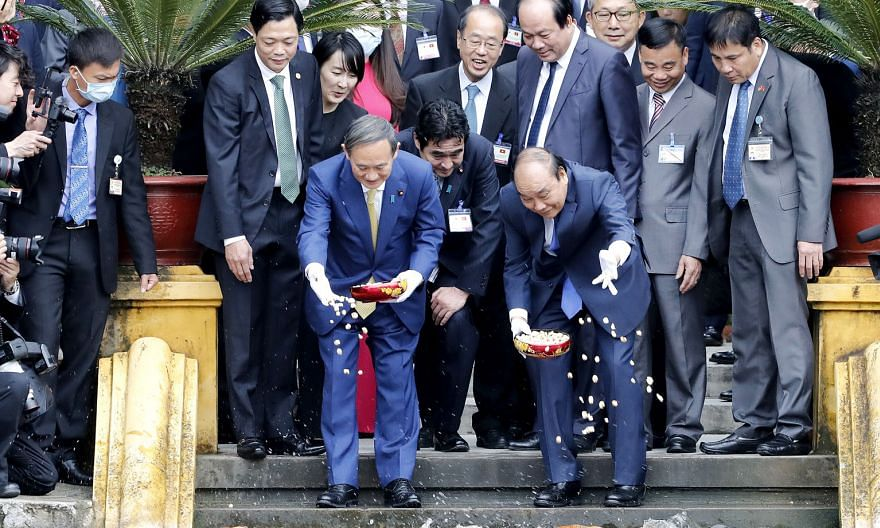 Japanese Prime Minister Yoshihide Suga (front row, left), on his first foreign trip since taking office, and his Vietnamese counterpart Nguyen Xuan Phuc feeding fish at the Presidential Palace compound in Hanoi yesterday. The two leaders stressed the