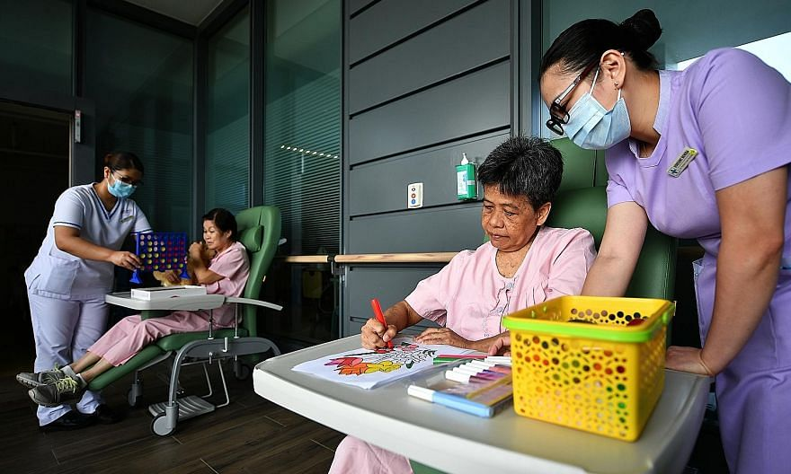 Staff nurse Cabreros Maria Fatima Nicolas (far left) and senior patient care assistant Bote Robenny Bovida (right) at a demonstration of a therapy session yesterday at Changi General Hospital's dementia ward. A survey at the ward found that more pati