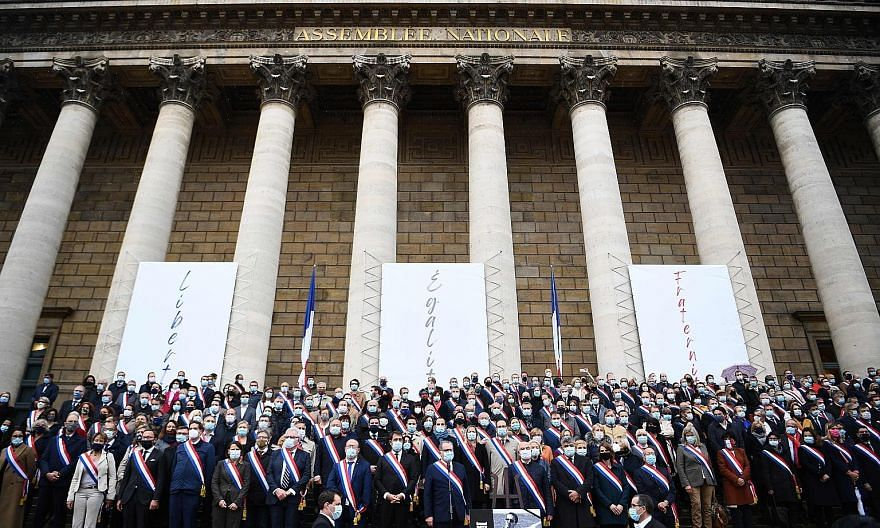 French MPs paying tribute, in front of the Palais Bourbon in Paris on Tuesday, to history teacher Samuel Paty, who was beheaded by an attacker for showing students cartoons of Prophet Muhammad in class.