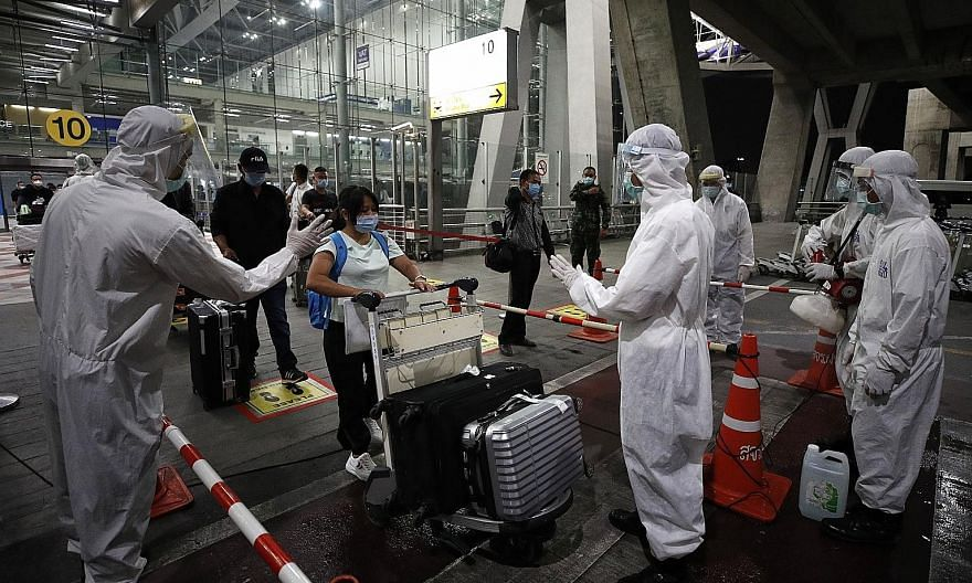 Chinese tourists going through arrival measures at Suvarnabhumi Airport on Tuesday. Thirty-nine tourists from Shanghai arrived on Tuesday night. Thai health officials in full protective equipment disinfecting the luggage of Chinese tourists upon thei